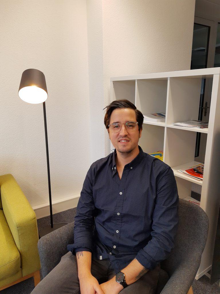 Julien Gödicke sitzt im Sessel der Sofaecke im Coworking Space.